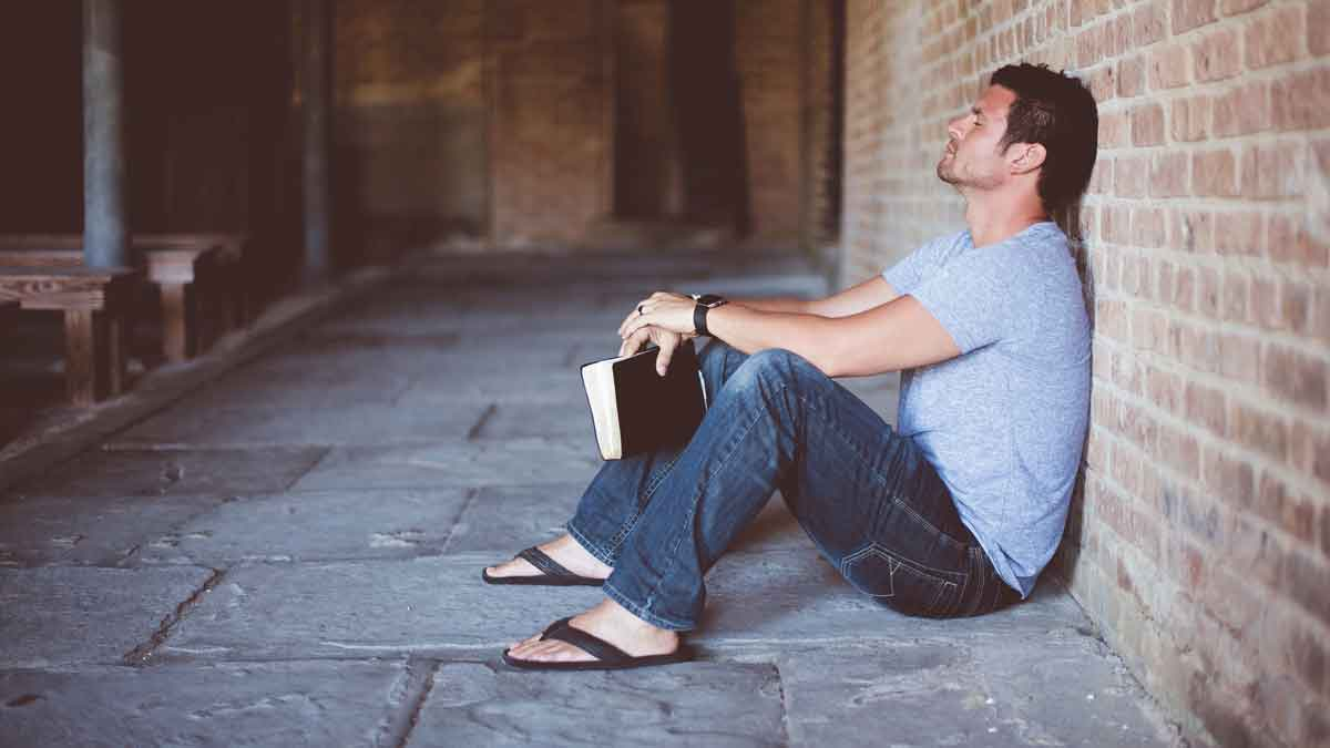 Man sitting against wall with bible in hand